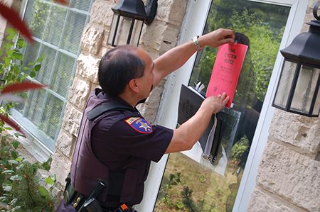 Officer placing an Eviction Notice on a door.
