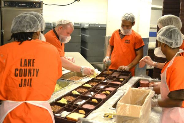 Inmates working in the kitchen making sandwiches.